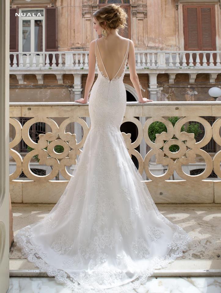 donna in abito da sposa in un balcone di una casa