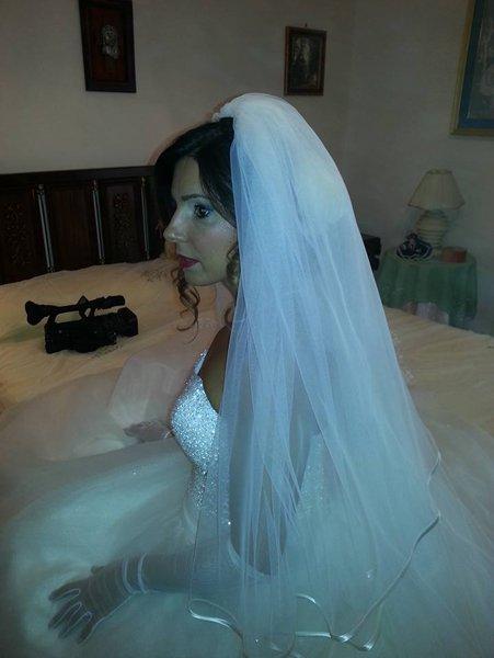 donna in abito da sposa seduta sul letto di una stanza