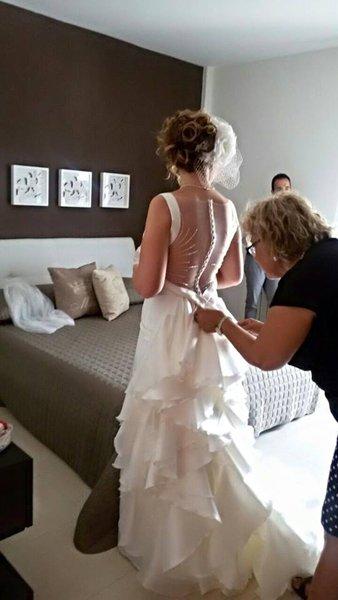 donna sistema il vestito della sposa in una camera da letto