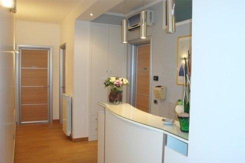 Ricezione della consultazione con moderni mobili di colore bianco combinato con l'uso del legno