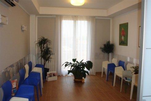 Calida sala d'attesa in toni chiari con sedie di colore blu e bianco