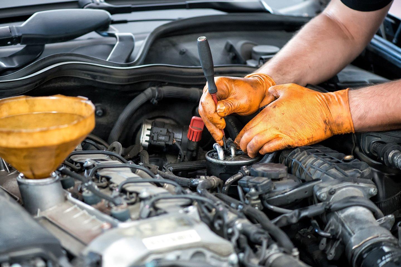 meccanico mentre ripara motore auto