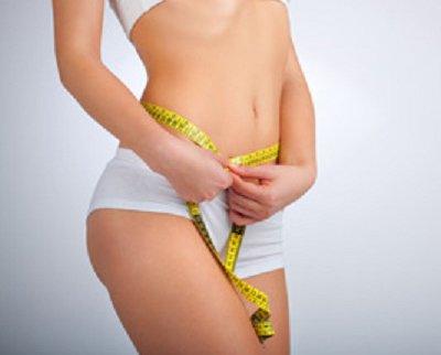 Donna in intimo che misura la circonferenza vita con un metro da sarta