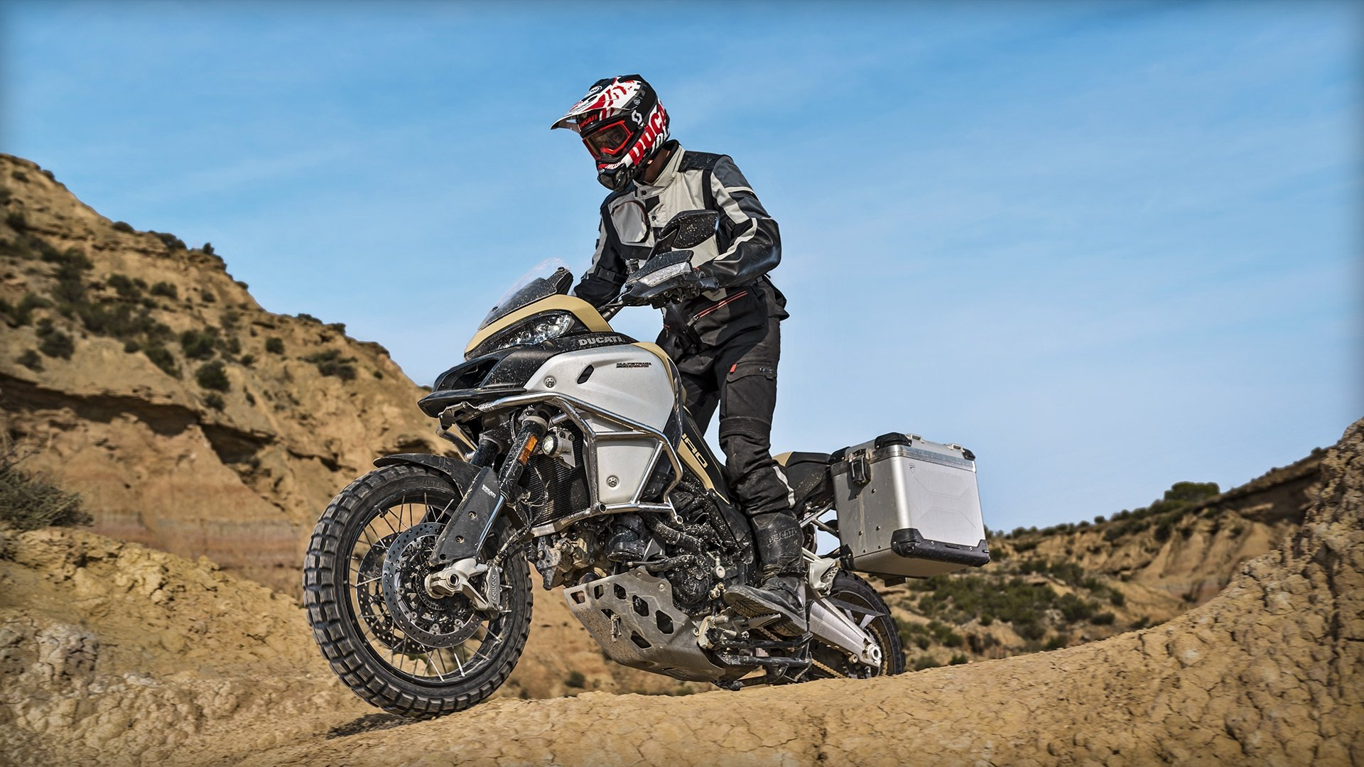 un motociclista con una tuta rossa e un casco bianco, rosso e nero che guida una Ducati bianca e nera su una strada sterrata e dietro vista delle montagne
