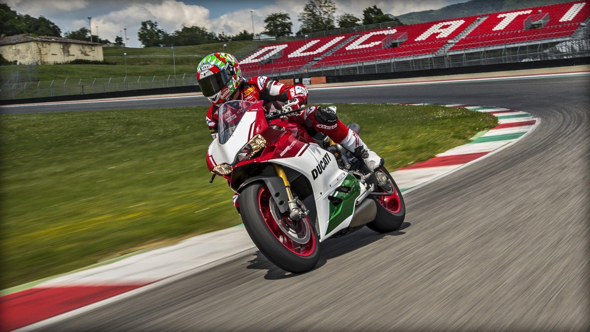 un motociclista che sta curvando con una moto da corsa rossa Ducati in una pista