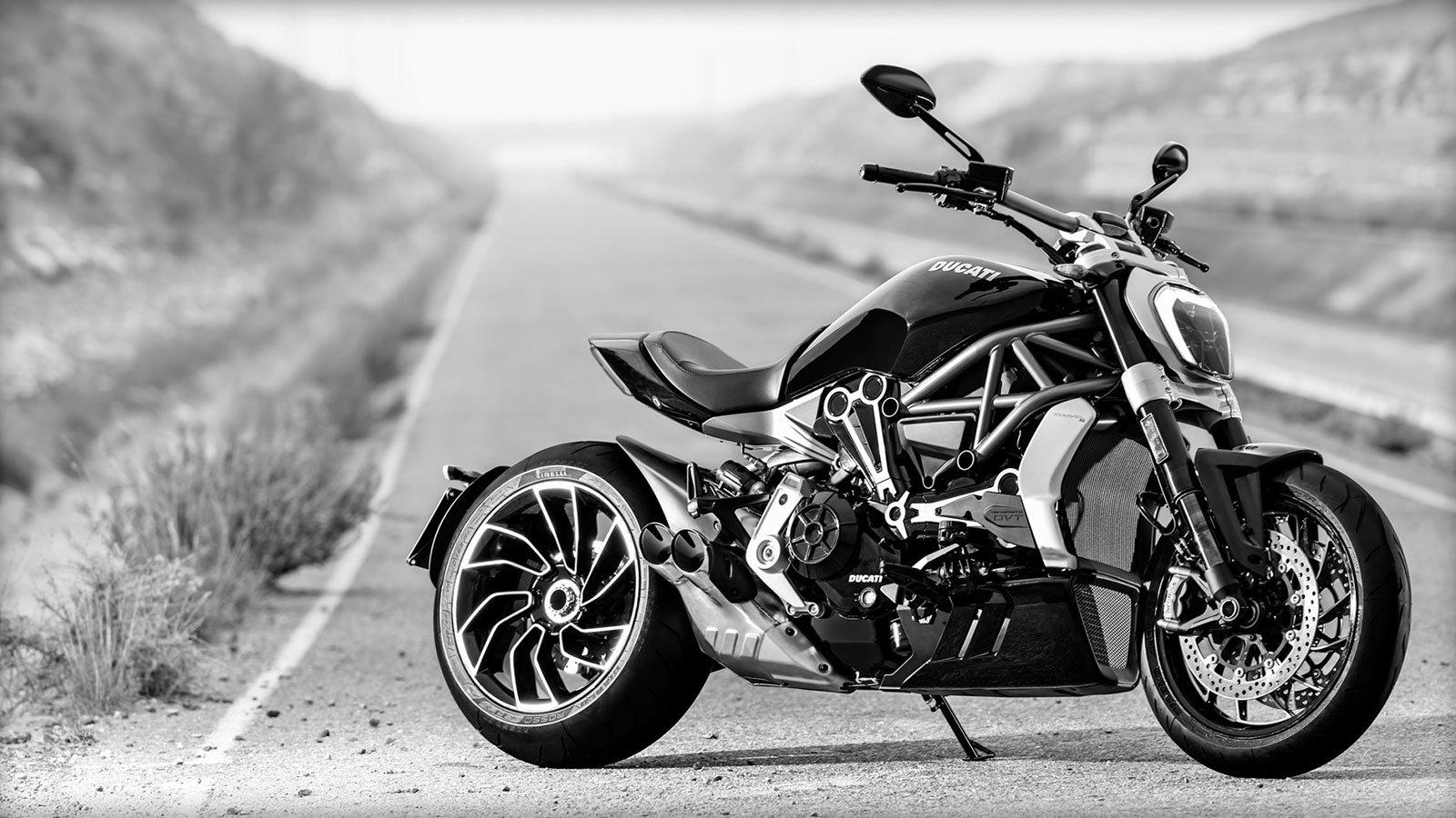 una moto Ducati color nero in una strada deserta in bianco e nero
