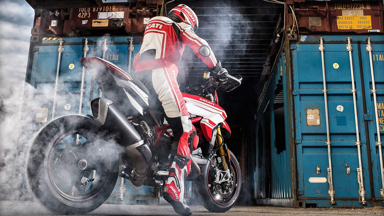 un motociclista con completo bianco e rosso Ducati mentre sta derapando con la moto e vista del fumo e davanti di alcuni container di metallo