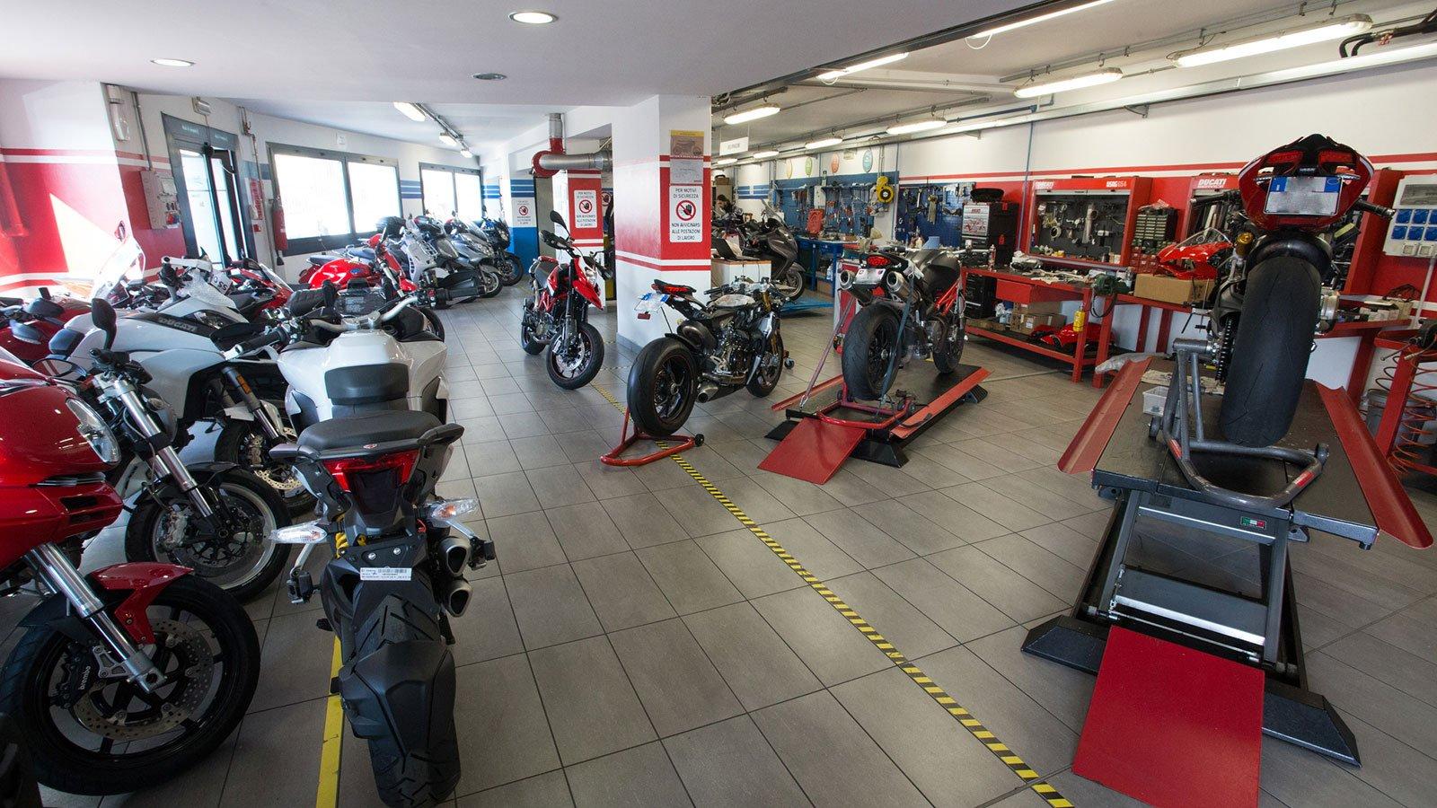 una serie di moto Ducati parcheggiate in un officina