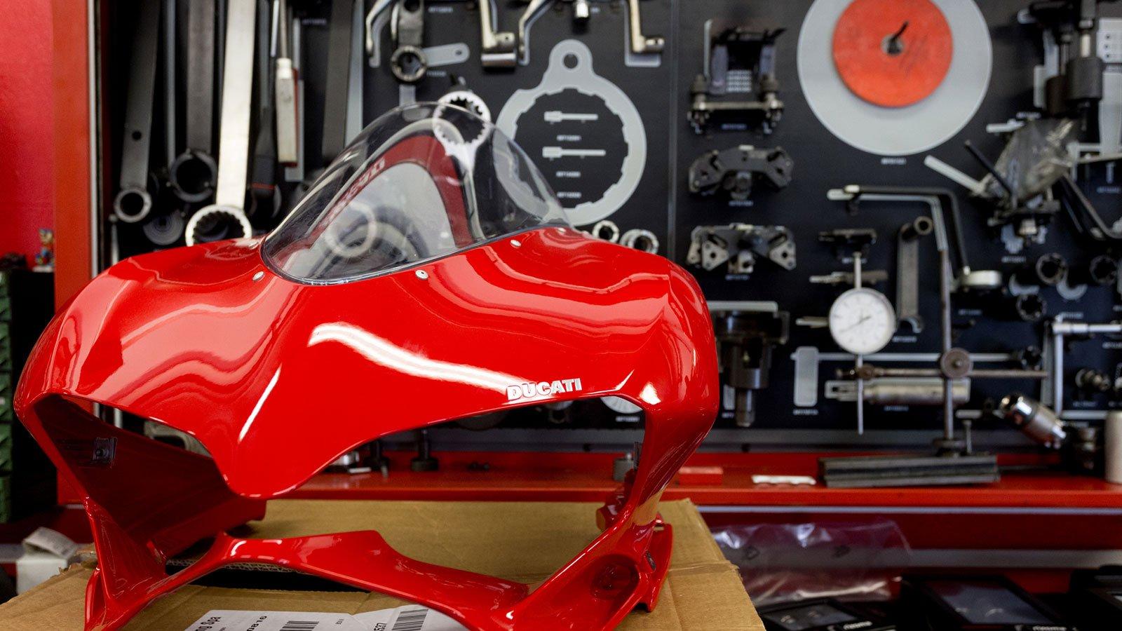 una carena anteriore di una Ducati di color rosso smontata e dietro degli attrezzi appesi al muro su un pannello