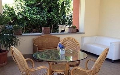 vista una sala da pranzo con tavolo in vetro, sedie e divano bianco