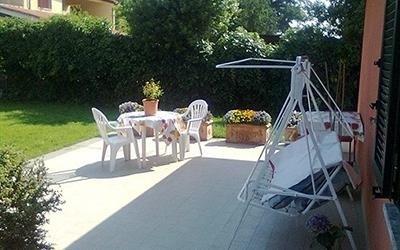 vista laterale di casa riposo con tavolo e sedie in un giardino