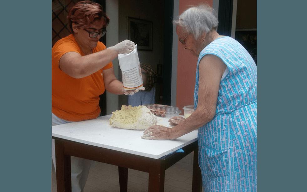 mani di una donne anziani in farina sistema per impastare la pasta su tabella