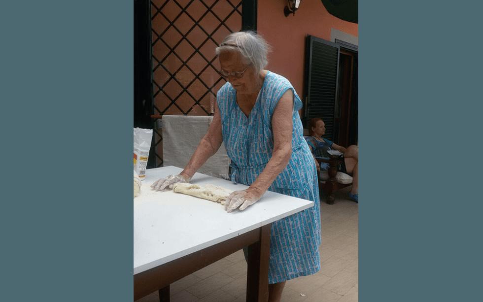 mani di una donna anziana in farina impastare la pasta su tabella
