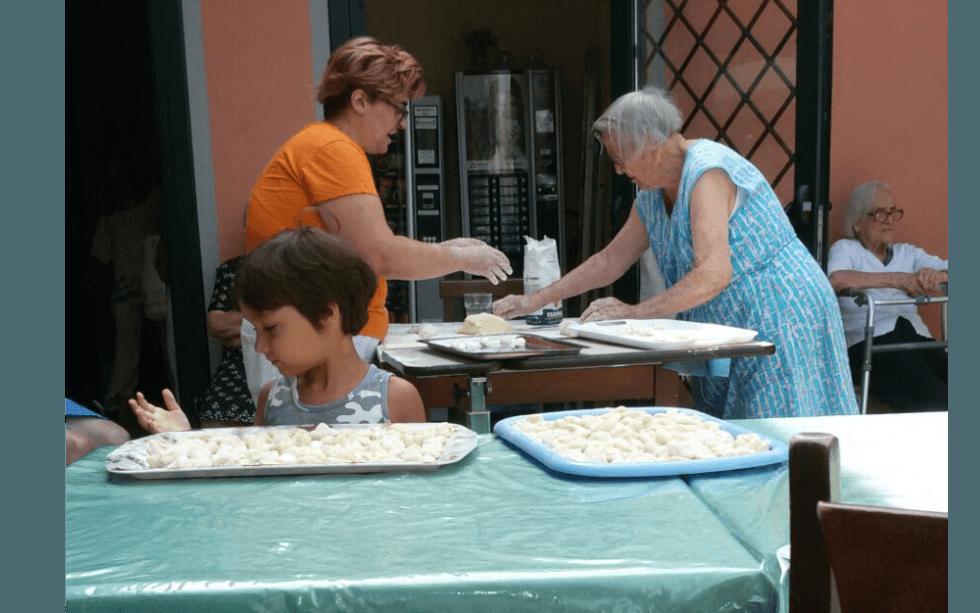 donne che impastano la farina mentre una bambina si guarda la mano davanti a un vassoio di pasta