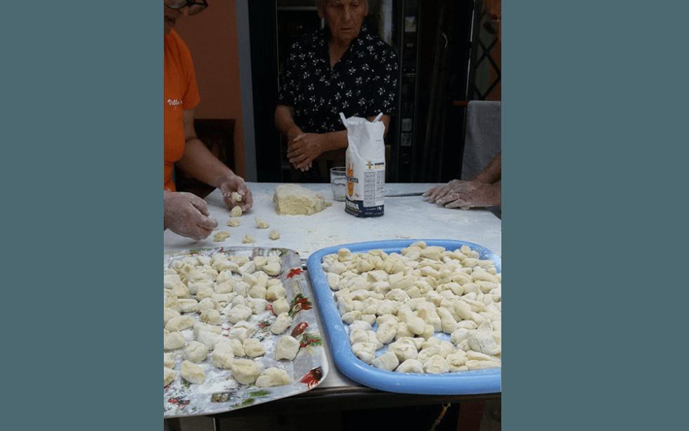 donne che preparano vassoi di gnocchi