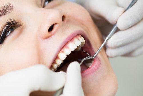 odontoiatra esamina denti con specillo e specchietto