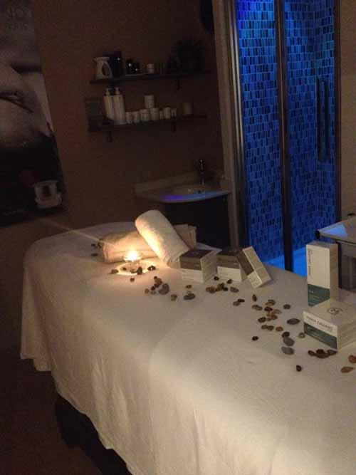 Immagine di un lettino da massaggio con sopra petali, prodotti di bellezza ed una candela accesa