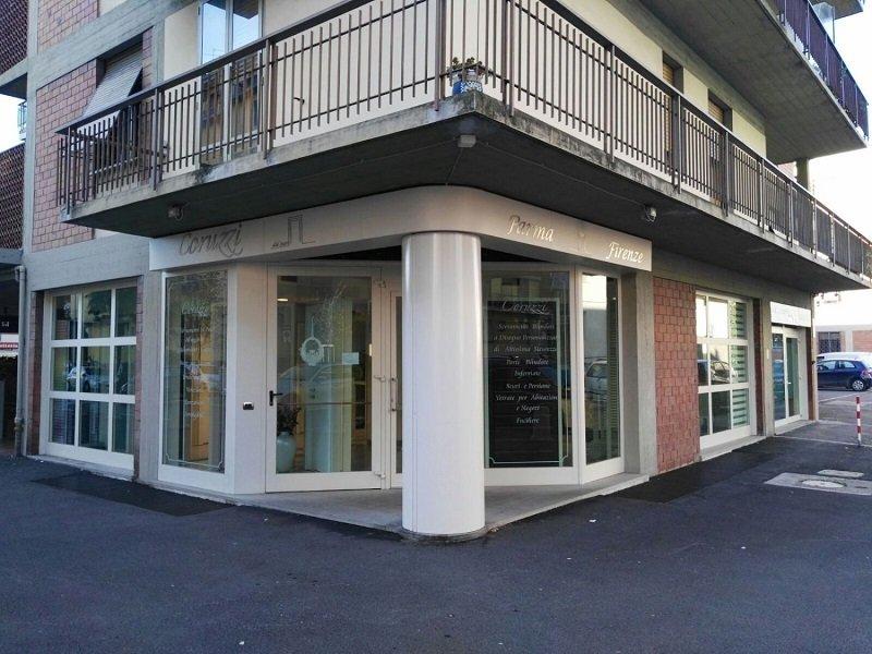 vista di uno stabile e sotto di un piccolo portico con delle vetrine con scritto Coruzzi