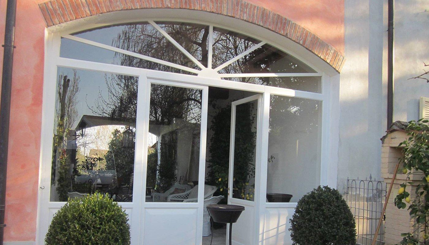 una porta finestra ad arco in vetro e legno bianco
