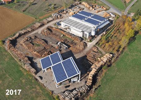 Vista aerea dell'officina di legno, le navi coperte di pannelli solari, tutte le legni separate per dimensioni