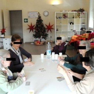 persone che giocano a carte in una struttura per anziani