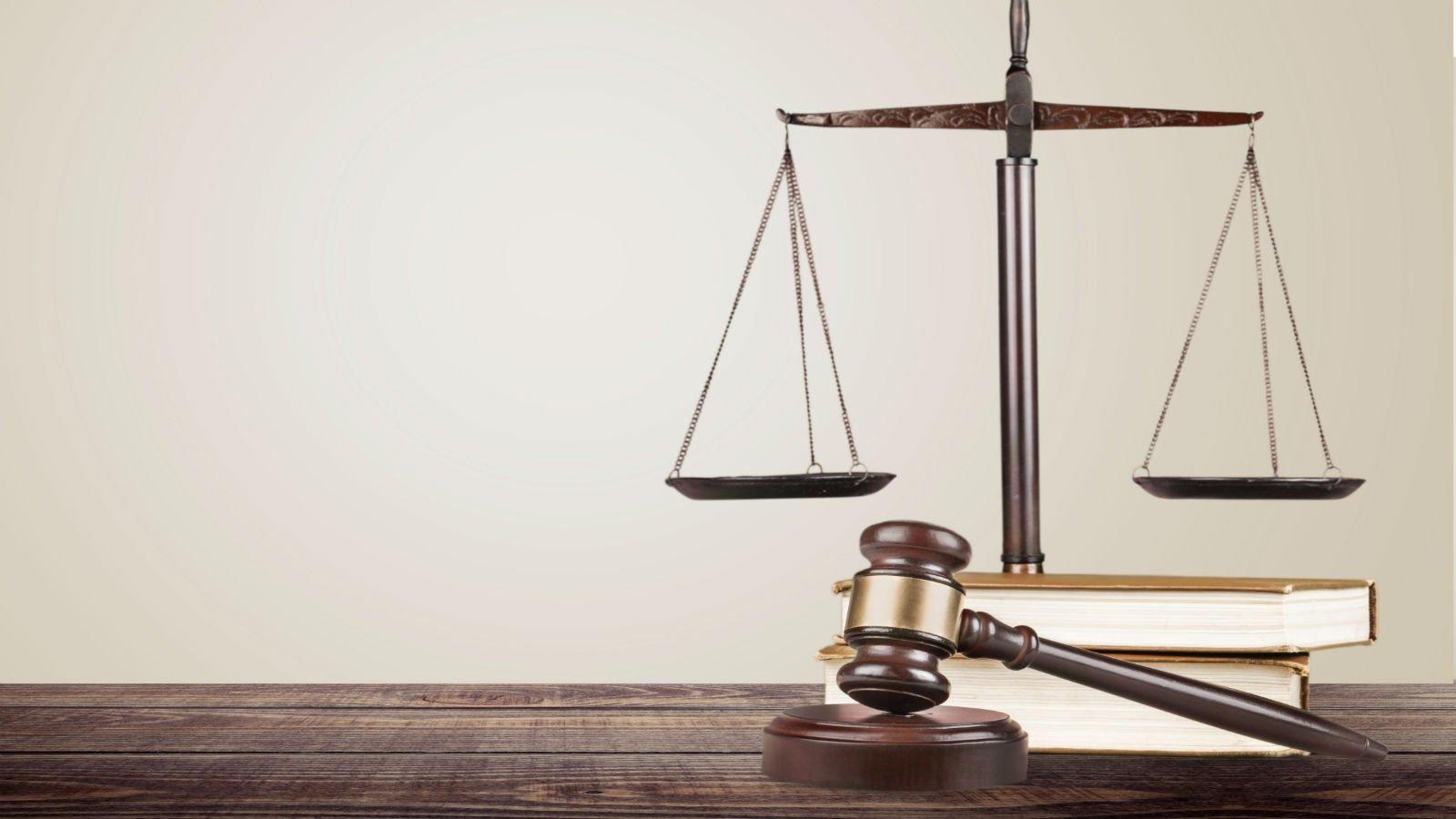 Due libri, la bilancia e la maza della giustizia su una tavola di legno