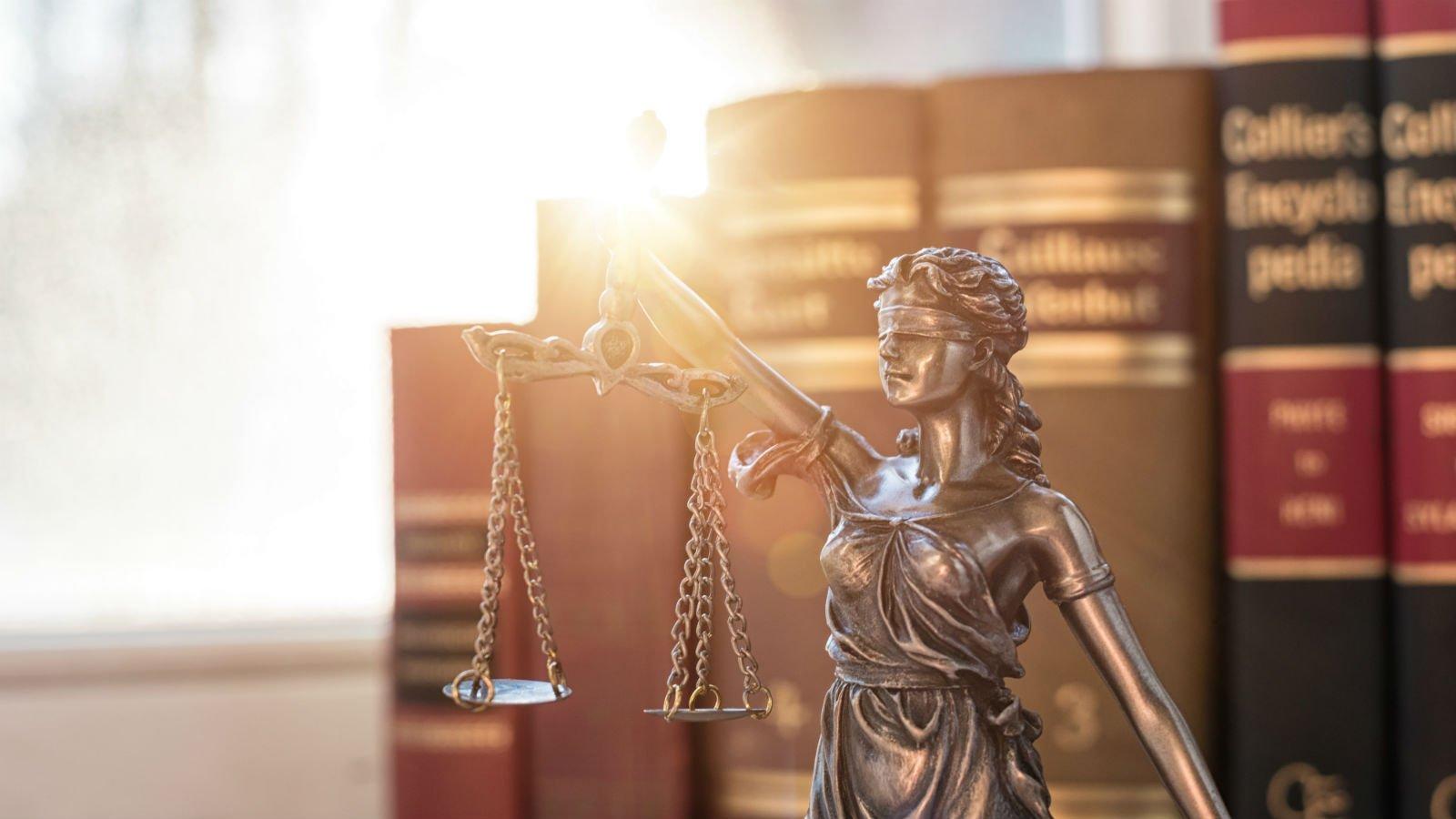 Primo piano di una statuetta di acciaio o di ferro vecchio della giustizia sostenendo la bilancia