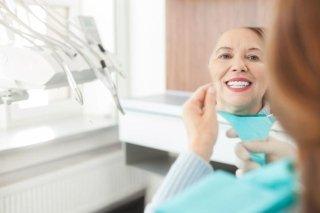 paziente si guarda allo specchio all'interno di studio dentistico
