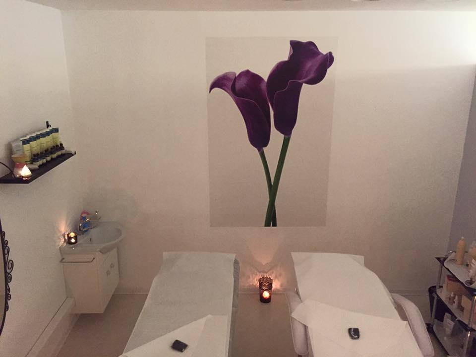 sala massaggi con due lettini, candele e un quadro con due fiori viola