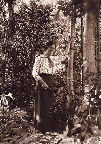 una foto in bianco e nero di una signora appoggiata a un tronco di un albero