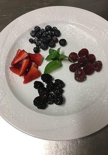 un piatto con dei frutti di bosco e fragole