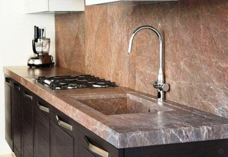 esempio di cucina in marmo rosso con lavello e rubinetto