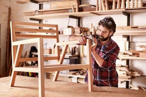 un uomo lavora una sedia di legno nella sua bottega