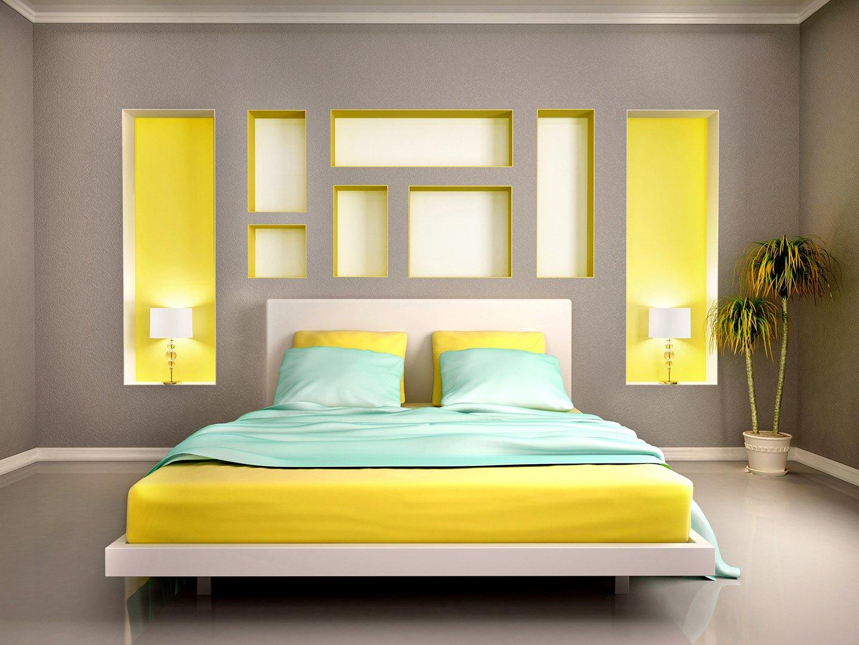 letto matrimoniale giallo con lenzuola azzurre e pareti bianche con arredamento grigio e giallo