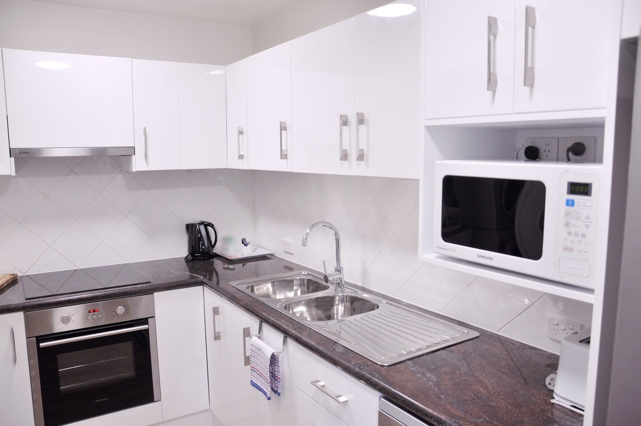 The modern fully equipped kitchen with laundry in our Two Bedroom deluxe Apartment 9