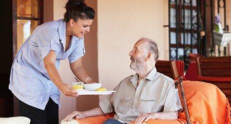A nurse serving breakfast