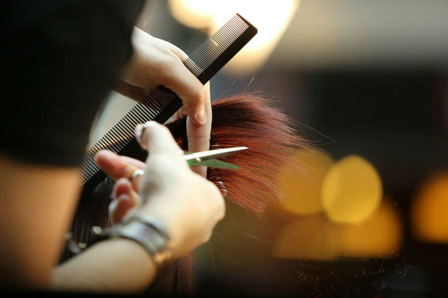 parrucchiera esegue taglio su capelli lunghi