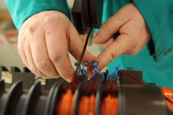 due mani che lavorano su dei fili di rame