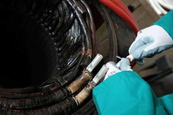 le mani di un operaio con dei tubi