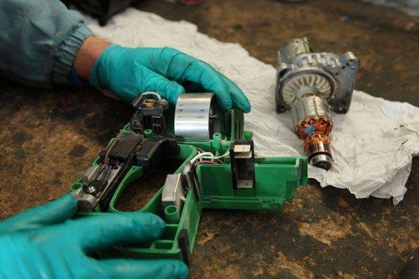 due mani di un operaio con un dispositivo elettronico disassemblato