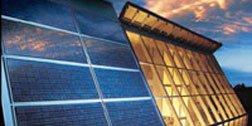 dei pannelli solari e accanto un palazzo con la facciata con delle vetrate