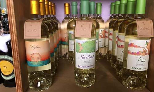 Vista di bottiglie di vino bianco di tre varietà diverse della cantina Donnafugata