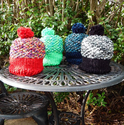 Special Edition colourful glow in the dark beanies on a garden table