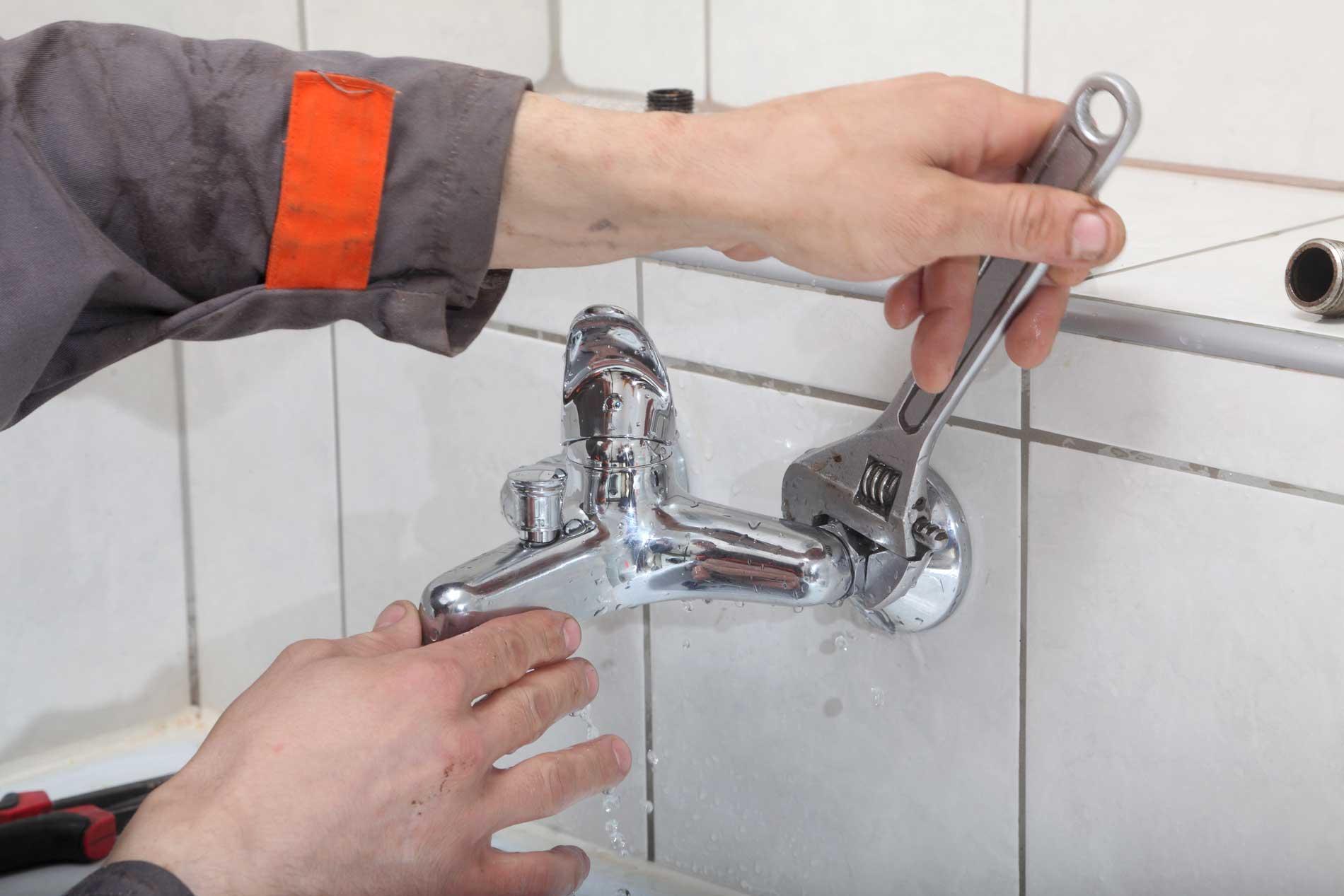 idraulico con chiave inglese durante manutenzione lavandino