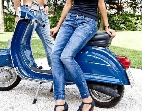 una Vespa blu con donna appoggiata sulla sella