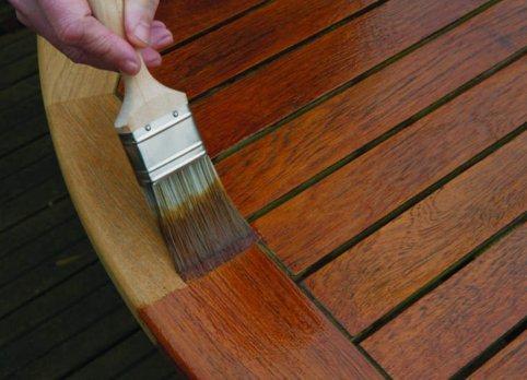 pennello stende prodotto per il legno sulla superfice di un tavolo