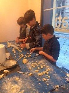 dei bambini mentre lavorano della pasta fresca