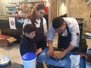un uomo che prepara una crostata e due bambini accanto che guardano