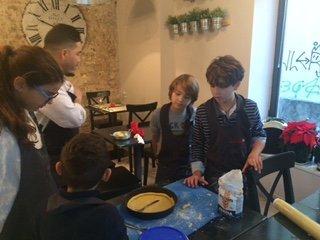 un uomo mentre insegna ai bambini come fare una crostata
