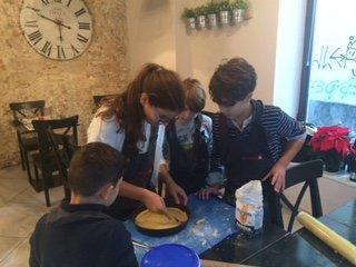 una bambina mentra fa dei piccoli buchi su una crostata e accanto altri bambini che guardano